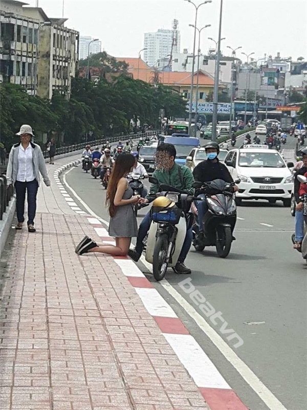 Cô gái quỳ gối trên cầu khiến không ít người đi đường tò mò. (Ảnh Internet)