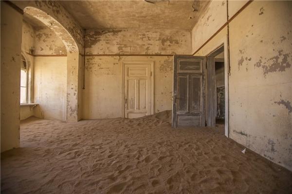 Sa mạc Namibia, Kolmanskop, Đức - nơi từng là chỗ trú ngụ của hàng trăm thợ mỏ xa xứ để tìm kiếm cơ hội phát triển - đã là một thị trấn thịnh vượng và trù phú trong 100 năm. Đến nay, thị trấn ma giữa sa mạc này chỉ còn mỗi cát bao quanh. (Ảnh: Getty Images)