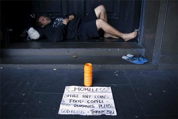 Một người hành khất đang nằmở lối thoát hiểm của tòa nhà ở Sydney, Úc.