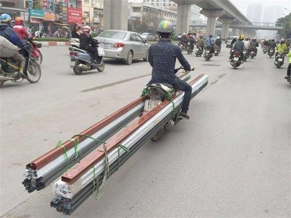 Không chỉ xe ba gác, đến những chiếc xe máy thế này cũng là phương tiện vận chuyển hàng chục thanh sắt dài.(Ảnh: Internet)