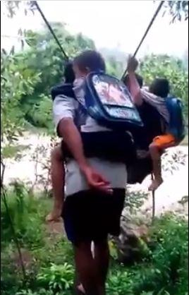 Hai người đàn ông cõng hai đứa bé đeo cặp học sinh chuẩn bị vượt suối (Ảnh cắt từ clip)