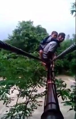 Một tay giữ đứa bé trên lưng, môt tay bám vào dây cáp (Ảnh cắt từ clip)