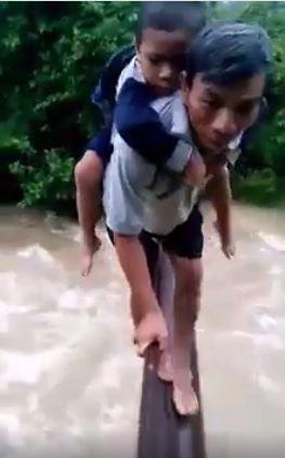 Nhận thấy sự nguy hiểm nên người đàn ông này đã cõng đứa bé vào lại bờ (Ảnh cắt từ clip) Sau đó ra giúp đỡ hai người còn lại nhưng chính anh ta cũng gặp nguy hiểm khi bị treo lơ lửng (Ảnh cắt từ clip)