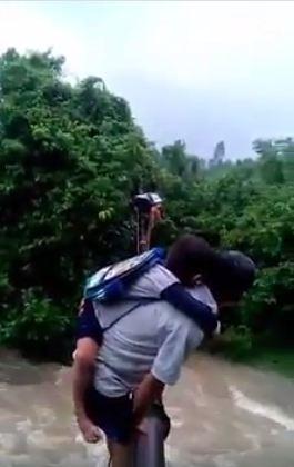 Đứa bé phải ôm chặt lấy người đàn ông(Ảnh cắt từ clip)