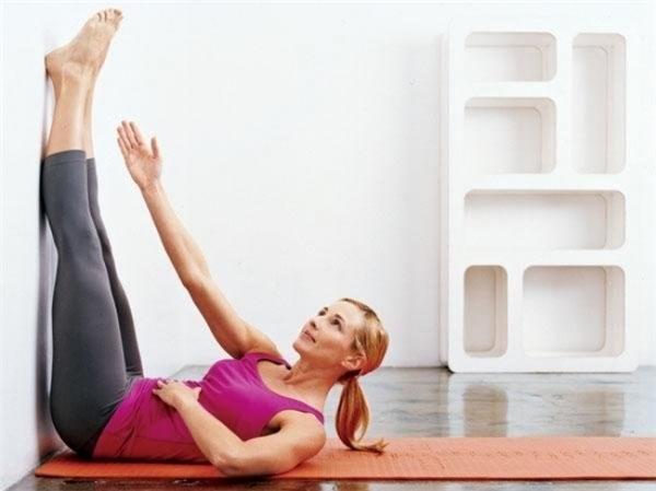 Tương tự hai bài tập trên, bạngiữ cơ thể nằm ngửa và mông đặt sát tường. Hai chân lúc này ép sát tường, duỗi thẳng và song song nhau. Tiếp theo, bạn rướn nửa thân trên lên kết hợpmột tay đặt trên bụng trong khi tay còn lại đưa thẳng, hướng về bàn chân, tạo hình như đang cúi chào. Tiếp tục giữ trong 5-30 giây rồi đổi bênlặp lại.