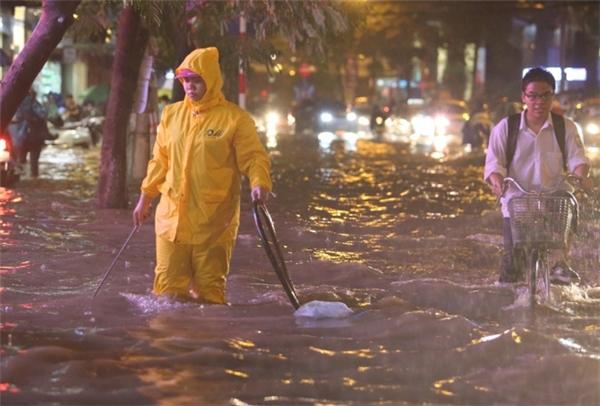 Nhân viên công ty thoát nước số 4 đi nhặt những vật cản, khơi thông dòng nước tại các nắp cống.Ảnh Phạm Ngọc Thành