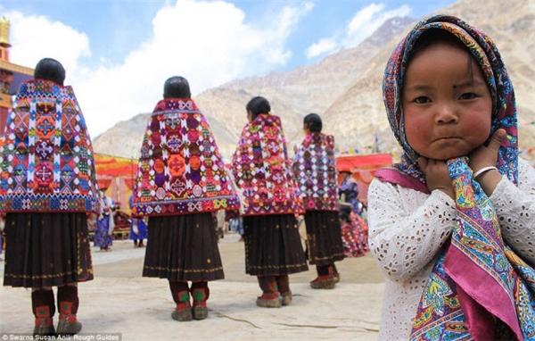 Một cô bé quấn chiếc khăn đầy sắc màu đứng sau lưng những người phụ nữ mặc trang phục truyền thống.