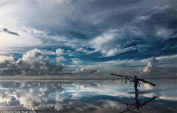 Người ngư dân như đang bước đi trên mặt nước trong bức ảnh chụp đồng bằng muối ấn tượng này.