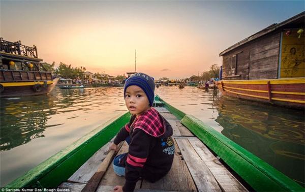 Cậu bé ngồi trên chiếc thuyền ngoái đầu lại nhìn người chụp.