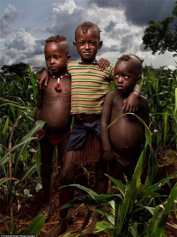 Ba cậu bé đứng giữa những bụi cây ở Ethiopia.