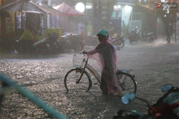 Cụ già dắt xe đạp đi giữa cơn mưa vì sợ bị ngã. Ảnh: Tứ Quý