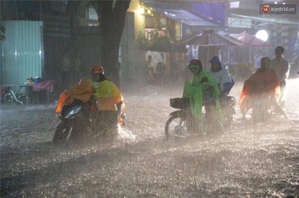 Nhiều người phải dắt xe máy đi qua đoạn đường ngập để tránh xe bị chết máy. Ảnh: Lê Giang