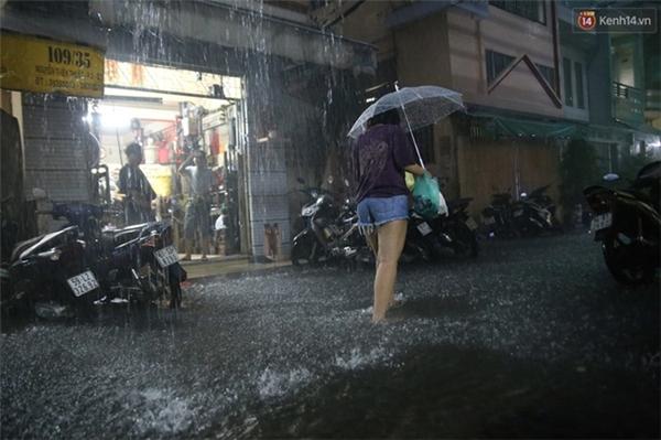 Cô gái lội nước trong con hẻm 109 đường Nguyễn Thiện Thuật, quận 3. Ảnh: Quỳnh Trân