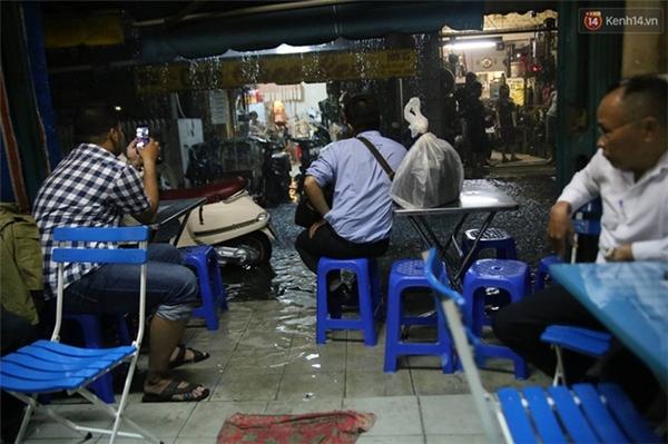 """Một quán cafe trên đường Nguyễn Thiện Thuật, Quận 3, nước đã ngập vào nhà. Cô Sương, chủ quán cho biết: """"Đây là lần đầu tiên con đường này ngập nặng đến vậy, mưa vẫn chưa ngớt nên mọi người đang rất lo lắng quán sẽ bị ngập vào sâu hơn"""". Ảnh: Quỳnh Trân"""