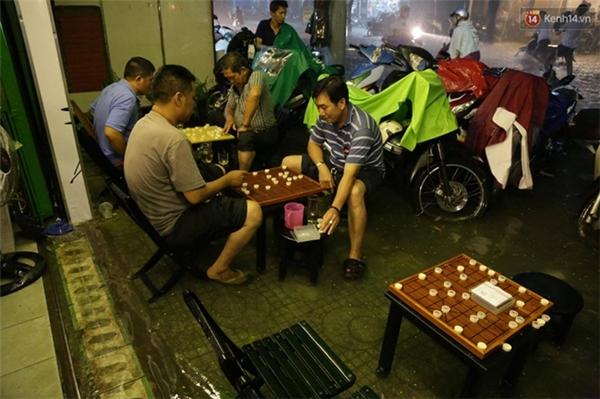 Nhiều người trú mưa ở quán cafe và tranh thủ chơi cờ. Ảnh: Lê Giang