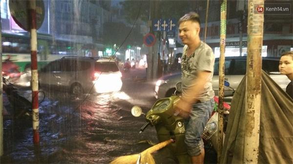 Người dân trên đường Điện Biên Phủ phải chạy ra trước nhà chỉ dẫn người tham gia giao thông tránh né những nơi có hố sụp và gờ chạy lên vỉa hè vì mưa quá lớn không chạy được. Ảnh: Lê Giang