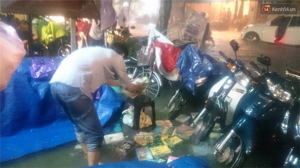 Một cửa hàng sách trên đường Nguyễn Trãi bị ngập nước, sách vở ở tiệm trôi lênh láng. Ảnh: Phạm An