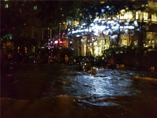 Nước lớn cùng dòng phương tiện di chuyển tạo thành sóng lớn như sông giữa đường phố. Ảnh: Vũ Nguyễn