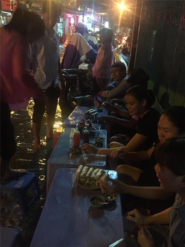 Một quán ăn ở đường Cống Quỳnh, cơn mưa đến bất chợt khiếnkhách hàng không thể ra về, đànhngồi lạitrên con ngõ ngập nước. Ảnh: Nguyễn Thu Thảo