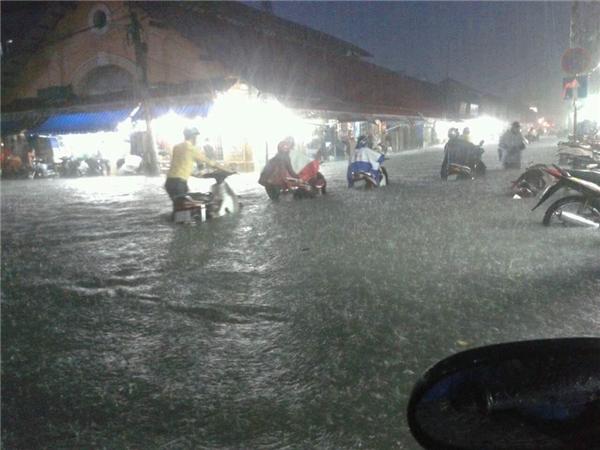 Đường phố trở thành sông, giữa cơn mưa lớn vẫn có nhiềungười đội mưa lội nước. Ảnh: Tuấn Nghĩa