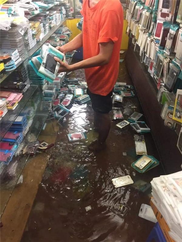 Trong một shop điện thoại di động tại quận 5,nước ngập toàn bộkhu trưng bày. Ảnh: Đạt Vũ Nguyễn