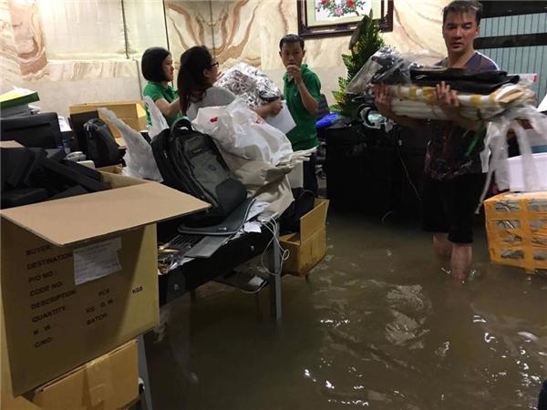 Nhà của Mr. Đàm cũng không khá hơn, nước lụt ngang ống đồng. Anh cũng phải cùng mọi người sơ tán đồ đạc. Ảnh: Thịnh Bùi