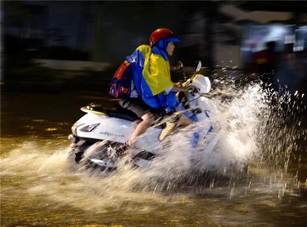 Ở một số nơi nước ngập ít hơn, sau vài giờ nước rút người dân đã có thể đi lại được phần nào. Ảnh: Ninh Doãn Hiếu
