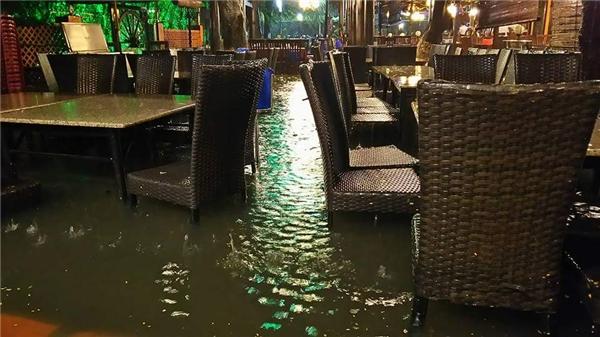 Một quán cà phêở Hồ Kỳ Hòa nước tràn cả lên thềm nhà, ngập toàn bộ bàn ghế. Ảnh: Đạt Vũ Nguyễn
