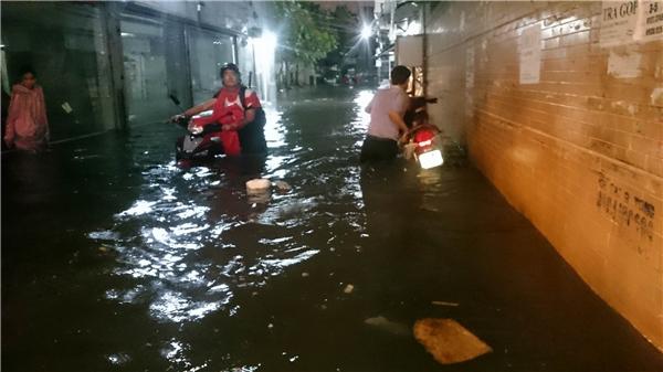 Nhũng con ngõ nhỏ trên phố Đinh Bộ Lĩnh nước chưa thoát kịp, đến 8h45 nước vẫn đang ngập ngang bụng người đi đường. Ảnh: Cương Trần