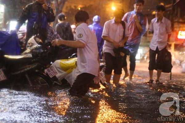 Cạnh đó, học sinh trường THPT Gia Định bì bõm lội nước về nhà sau giờ tan trường.