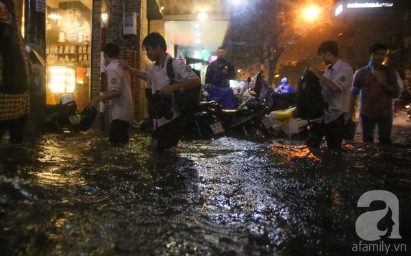 Nước ngập sâu, học sinh phải cầm theo giày, lội chân đất.