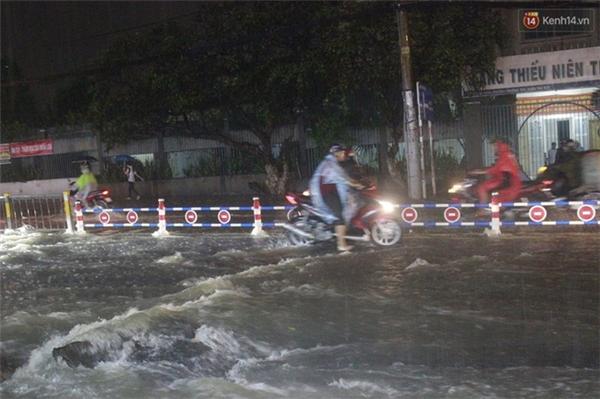 Nhiều người điều khiển xe máy cố gắng đi qua đoạn đường ngập.