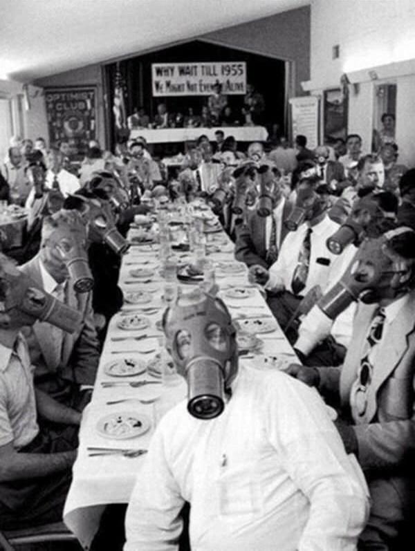 """Các thành viên của Hội những người lạc quan Highland Parktại một bữa tiệc với những chiếc mặt nạ phòng độc vào năm 1954. Đằng xa là khẩu hiệu: """"Sao phải đợi đến năm 1955 trong khi ta thậm chí không thể tồn tại nữa?"""". (Ảnh: Internet)"""