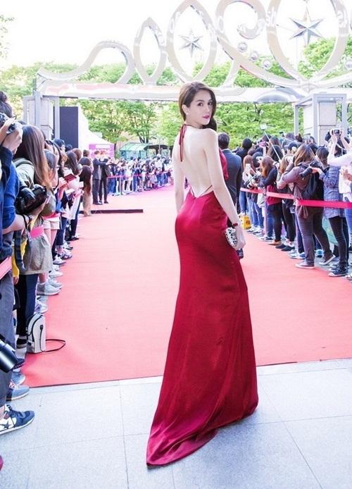 """Cũng trong năm 2015 vừa qua, Ngọc Trinh cùng dàn chân dài của ông bầu Vũ Khắc Tiệp đã đến Hàn Quốc để nhận giải """"Nữ hoàng bikini Châu Á"""" tạilễ trao giải Asia Model Awards 2015 diễn ra hoành tráng tại sân vận động Olympic Seoul.Trên thảm đỏ, sân khấu, Ngọc Trinh cuốn hút mọi ánh nhìn khi diện bộ váy màu đỏ sang trọng, quyến rũ, chất liệu mềm mại. Thiết kế cổ yếm giúp người đẹp khoe được lưng trần quyến rũ. Tuy nhiên, bộ váy cũng bị cho rằng """"đạo"""" thiết kế mà Nong Poy từng diện."""