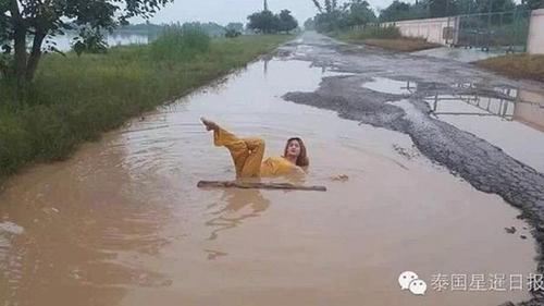 Một phụ nữ ở tỉnh Chaiyaphum, đông bắc Thái Lan, cũng nằm giữa vũng bùn trên con đường để tạo dáng.