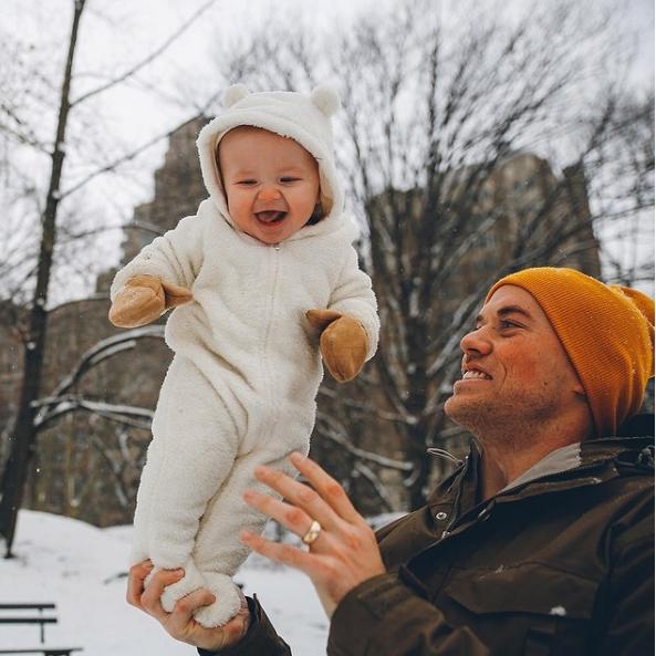 Cô công chúa bé nhỏ vui cười hạnh phúc trên bàn tay mạnh mẽ của cha.