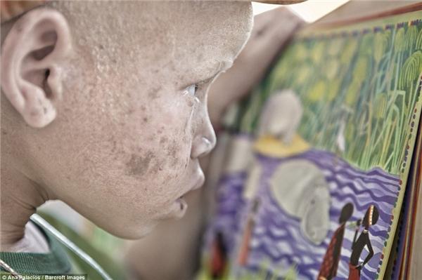 Một bé gái đang xem lại tác phẩm nghệ thuật của mình.
