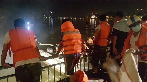Trên bờ, lực lượng cảnhsát đứng chờ vận chuyển cá để đóng vào những chiếc bao chuyển đi.