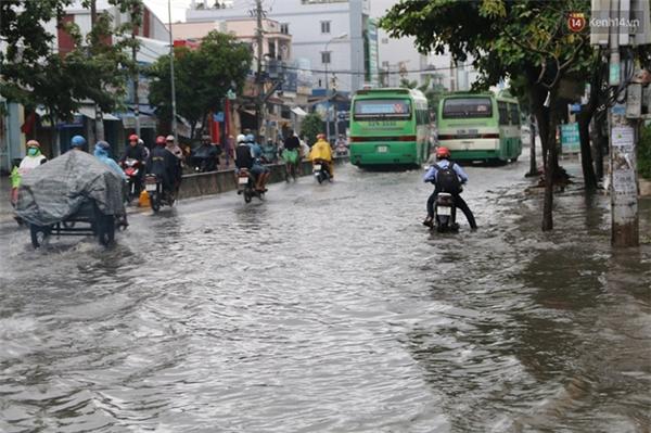 Nhiều người chật vật đi qua đoạn đường ngập nước.