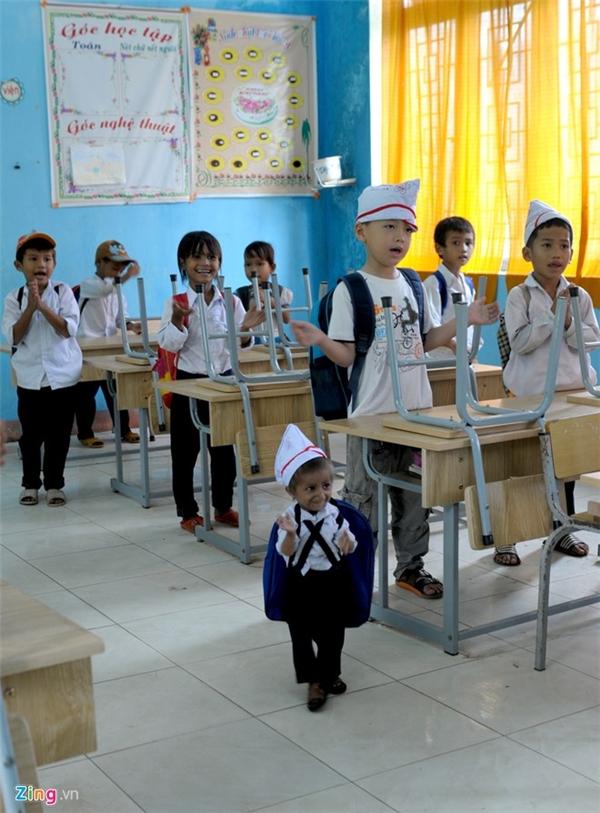 Giờ tan học, K'Rễ vỗ tay cùng các bạn chào cô giáo. Theo thầy Cương, trường đã đặt may một số bộ đồng phục quần xanh, áo trắng, mũ và bốn đôi giày da phù hợp đôi bàn chân bé xíu của em.