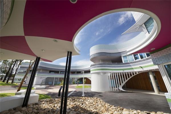 Những bức tường nghiêng hay uốn lượn cùng màu sắc tươi sáng tạo nên vẻ hài hước, năng động cho ngôi trường này.