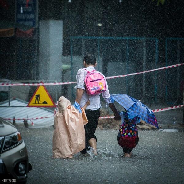 Hìnhảnh người cha chấp nhận ướt sũng, dành áo mưa và ô cho con khiến nhiều người xúc động.