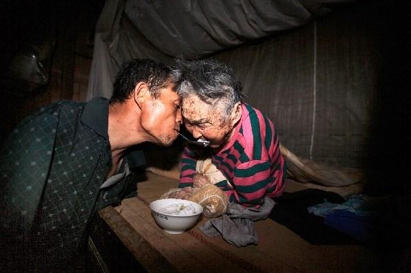 Khimẹ ông bị ốm nằm liệt giường, ông đã dùng miệng ngậm từng muỗng thức ăn, miếng cháo đútcho mẹ.