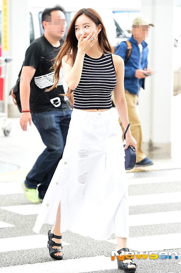 Hyomin vô cùng thời trang khi kết hợp chân váy denim trắng dáng dài cùng áo thun ba lỗ kẻ sọc.
