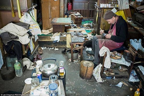 Một cụ ông là thế hệ thứ ba sửa giày của gia đình vẫn cần mẫn làm việc.
