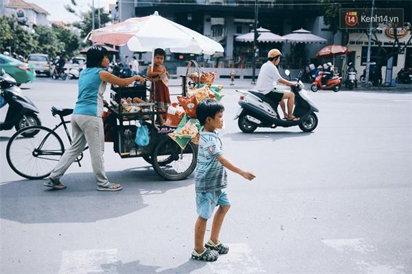 Chị Úy cùng các con đi dọc đường Phan Xích Long, quận Phú Nhuận để lượm ve chai và bán bánh snack.