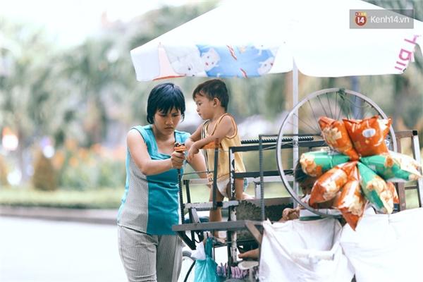 Vì chồng chạy xe ôm cả ngày, lại không có người thân thích nên chị Úy phải vừa đi bán vừa chăm sóc con trên chiếc xe đẩy hàng này.