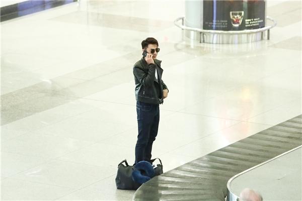Nam ca sĩ bận rộn trả lời những cuộc điện thoại ngay khi vừa xuống máy bay. - Tin sao Viet - Tin tuc sao Viet - Scandal sao Viet - Tin tuc cua Sao - Tin cua Sao