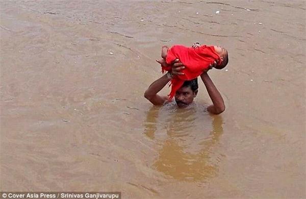 Quá lo lắng cho sức khỏe ngày một yếu đi của con, anh Pangi đã quyết định vượt qua dòng nước lũ đầy nguy hiểm hơn hàng chục cây sốđể đến trung tâm y tế.