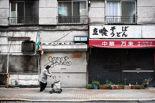 Trên vỉa hè thuộc một khu phố ở Tokyo,một cụ bà khác đang từ tốn đẩy chiếc xe từng bước thận trọng.